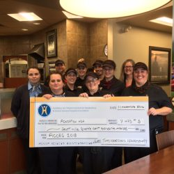 A group of Tim Hortons' employees hand a cheque for $7,473 for the Smile Cookie campaign 2016.