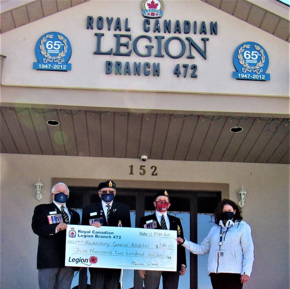 Three representatives from the Royal Canadian Legion and Ladies' Auxiliaires hand a big cheque to the Foundation representative.