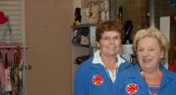 Two smiling ladies volunteer at HGH and wear their blue coat